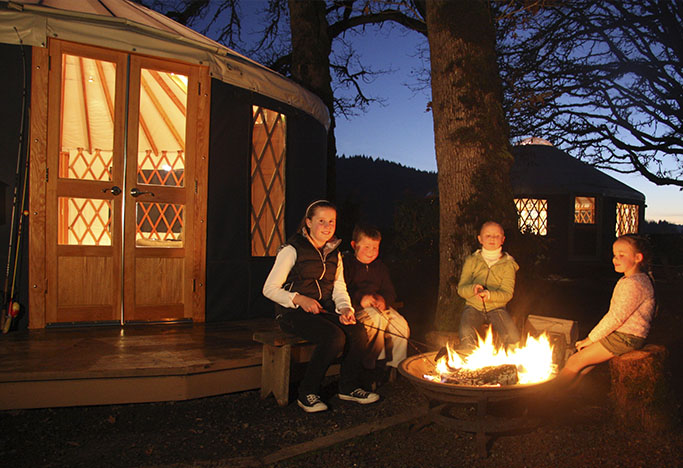 Happy yurt camper kids by the fire