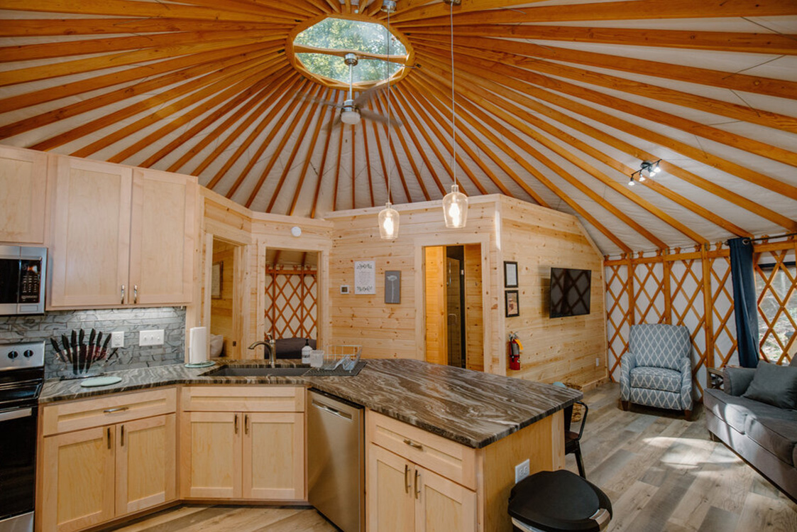 Kitchen space of a Pacific Yurt with light wooden walls.