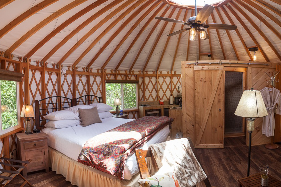Queen size bed in a yurt bedroom with a large two door dresser and hanging fan.