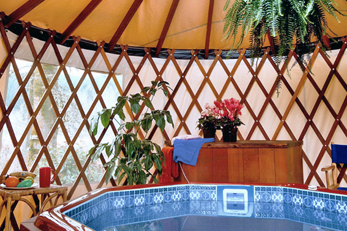 Hot tub inside of a yurt next to a wooden dresser with a blue towel and flowers on top.